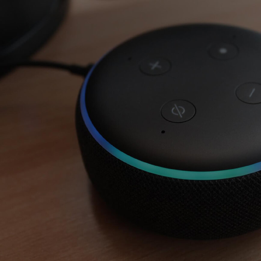 Image of an Amazon Alexa device sitting on a table with a dark overlay