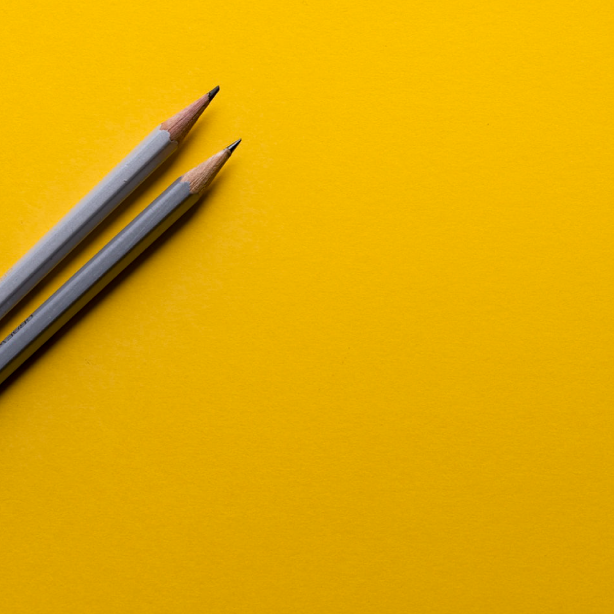 Two gray pencils for writing alt text for a website sitting on a yellow background