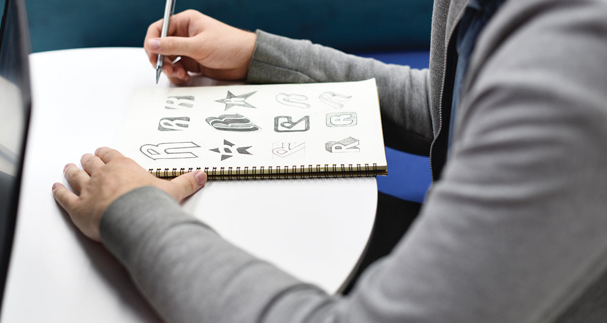 man sitting at a desk with a drawing pad with drawn logos