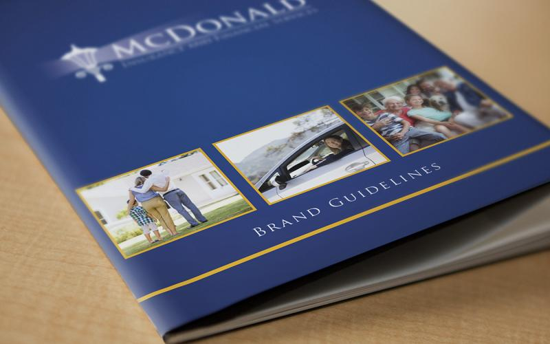 Close up of brand standards guide cover that has McDonald Insurance logo and text that reads 'brand guidelines'
