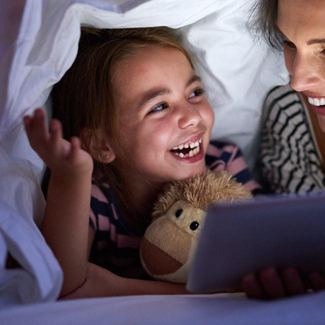 a mother and daughter reading a book in bed
