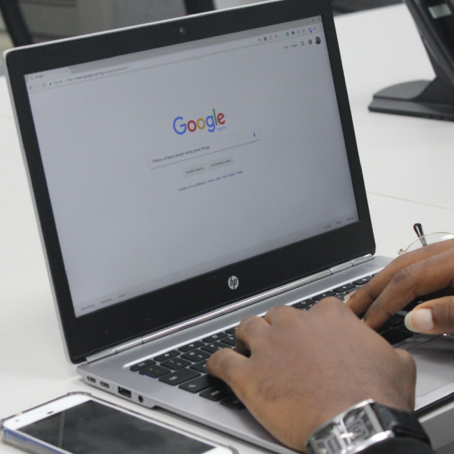 "Laptop on desk with persons hands typing on keyboard and ""Google"" on the screen"